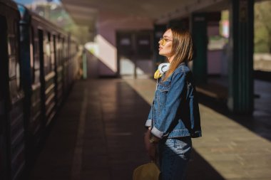 side view of stylish woman in sunglasses with headphones standing at outdoor subway station