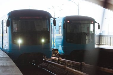front view of two trains at outdoor subway station
