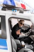 lächelnd Polizistin im Streifenwagen sitzen