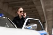 Fotografie Polizistin sprechen per Funk in der Nähe Polizeiauto