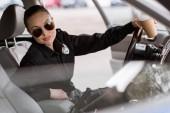 Fotografie attraktive Polizistin mit Pappbecher Kaffee im Auto sitzen und Blick in die Kamera