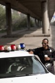 Photo police officer with coffee to go leaning on police car on street
