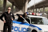 Photo young police officers standing near car under bridge