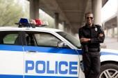 gut aussehend afroamerikanischen Polizisten mit verschränkten Armen wieder auf Auto gelehnt und Blick in die Kamera