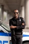 Fotografie Afrikanische amerikanische Polizisten Lächeln mit verschränkten Armen wieder auf Auto gelehnt und Blick in die Kamera