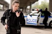 Fotografie junge attraktive Polizistin mit Walkie-talkie mit unscharfen Partner in Ihrer Nähe Auto auf Hintergrund