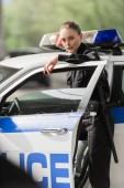 Fotografie Polizistin Stand in der Nähe Polizeiauto unter Brücke Blick in die Kamera Lächeln