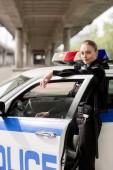Polizistin Stand in der Nähe Polizeiauto unter Brücke Blick in die Kamera