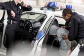 Fotografia ritagliata colpo della poliziotta parlando radio impostata mentre il suo compagno immissione arrestato uomo in automobile