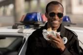 s úsměvem africké americké policista v sluneční brýle s burger v ruce u auta