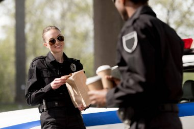 police officers with coffee to go and paper bag with lunch having break