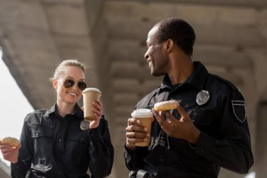 young police officers having coffee break with doughnuts