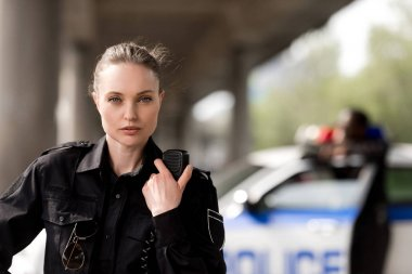policewoman using walkie-talkie and looking at camera with blurred partner near car on background