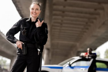 Happy attractive policewoman using walkie-talkie with blurred partner near car on background stock vector