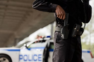 Cropped shot of police officer taking out gun stock vector
