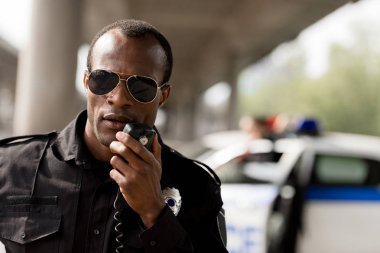 african american police officer talking by walkie-talkie radio set