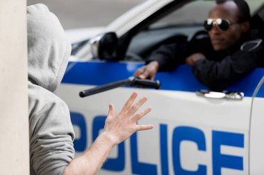 police officer peering out car window and pointing at hooded man with police bat