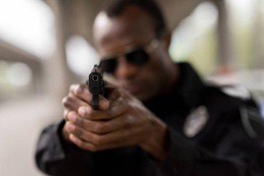 Closeup shot of handgun in hands of african american policeman stock vector