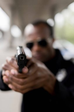 closeup view of black pistol in hands of policeman