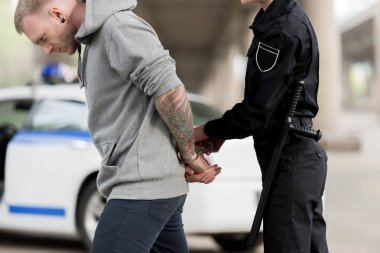 cropped shot of policewoman handcuffing young male bandit