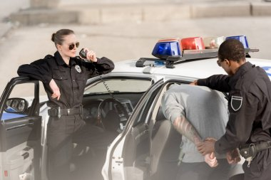 young policewoman in sunglasses talking on radio set and policeman with arrested bandit