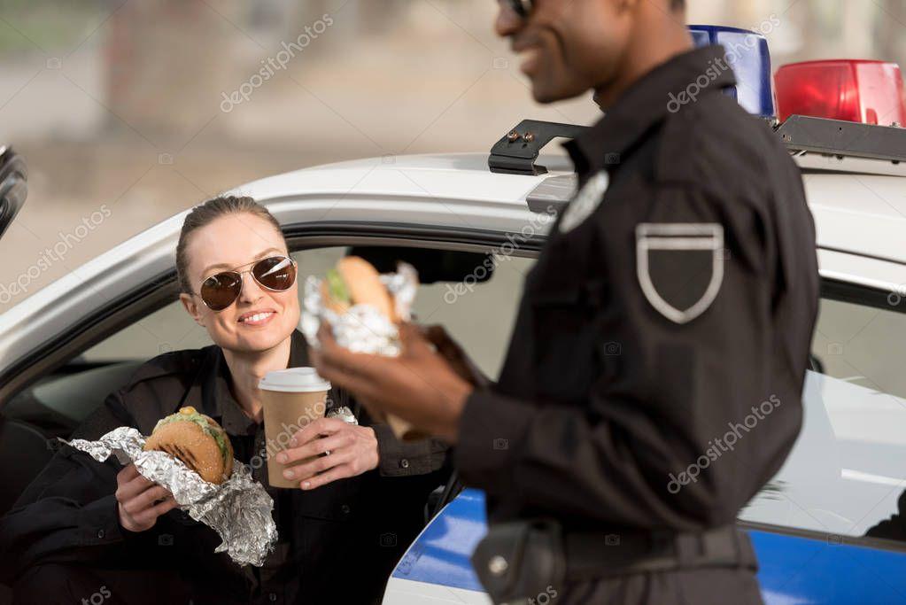 アフリカ系アメリカ人の警官をコーヒー カップを保持している女性警察官と昼食のクロップ撮影 — ストック画像