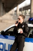 Photo policewoman in sunglasses talking on portable radio and holding burger near car