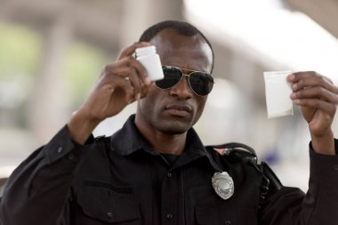 african american policeman holding drugs in plastic zipper and pills jar