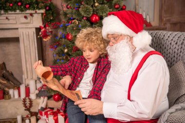Santa Claus and child reading wishlist