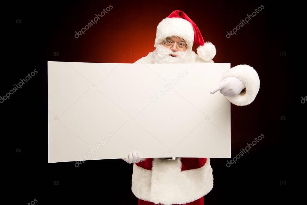 Santa Claus pointing on blank card