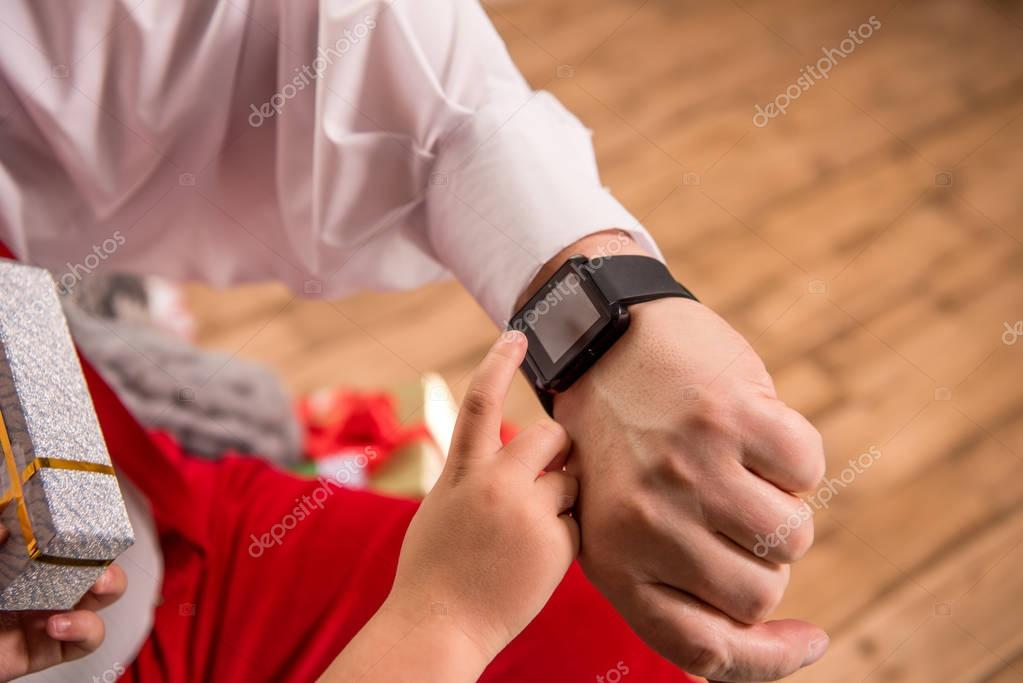hand with smartwatch and child finger