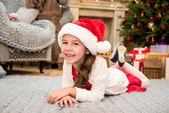 Kind mit Weihnachtsmütze auf Teppich liegend