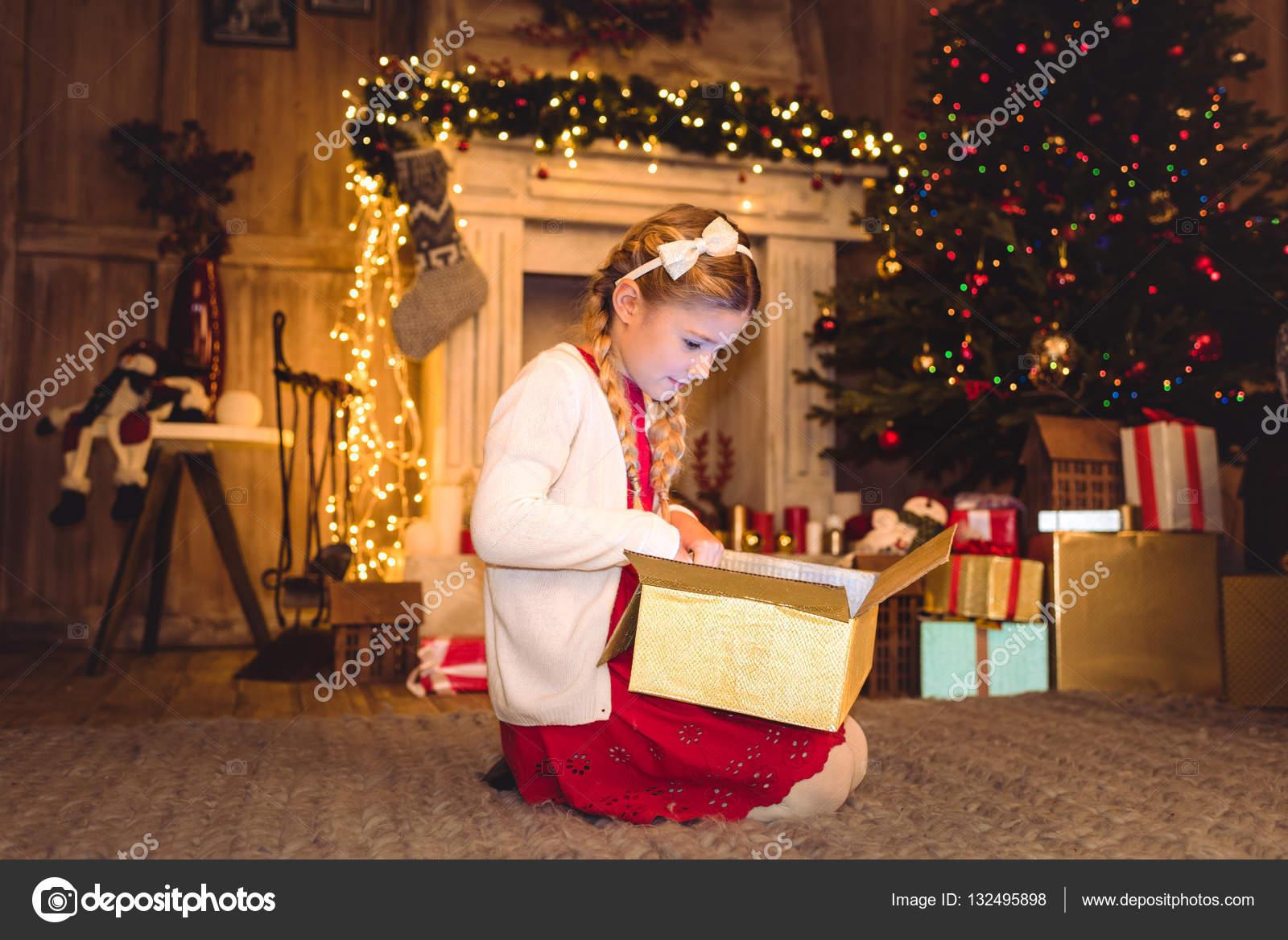 Mädchen öffnen Weihnachtsgeschenk — Stockfoto © SergKovbasyuk #132495898