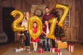 Šťastná rodina drží zlaté balónky