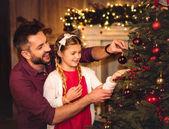 Fotografie Vater und Tochter schmücken Weihnachtsbaum