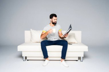 Bearded man reading magazine
