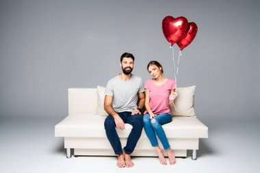 Couple sitting on couch with red balloons