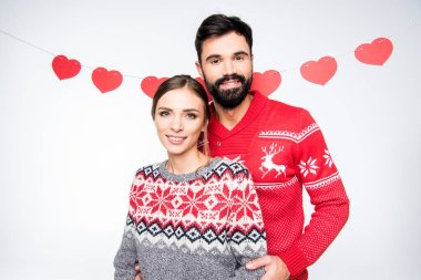 Smiling couple in knitted sweaters looking at camera isolated on white stock vector