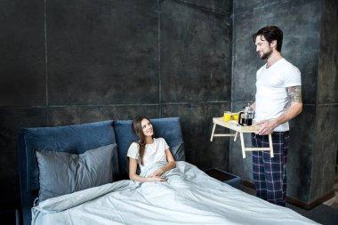 Man brings breakfast in bed