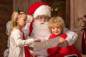 Fotografie Children showing picture to Santa Claus