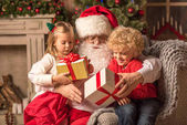 Santa Claus with children holding gift boxes