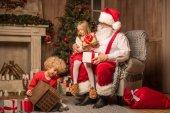 Fotografie Santa Claus with children sitting near fireplace