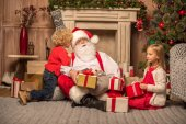 Fotografie Santa Claus and children with Christmas gifts