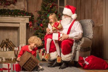 Santa Claus with children sitting near fireplace