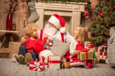 Santa Claus and children with Christmas gifts