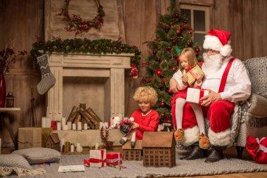 Santa Claus and children sitting near fireplace