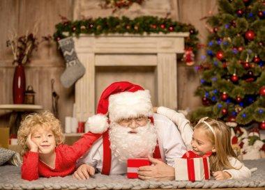 Santa Claus and children lying on carpet
