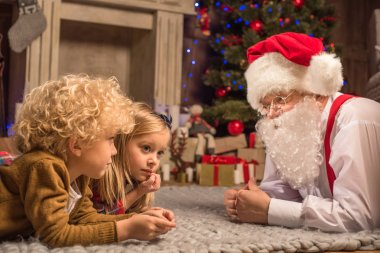 Children and Santa Claus lying on carpet
