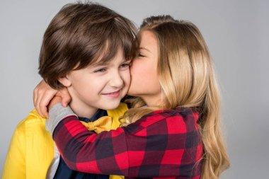 Portrait of schoolgirl hugging and kissing in cheek smiling schoolboy on grey stock vector