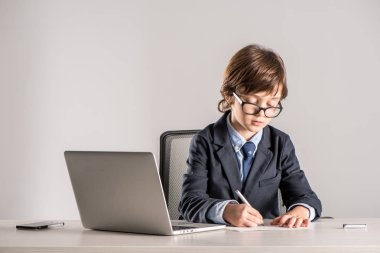 Schoolchild in business suit writing documents